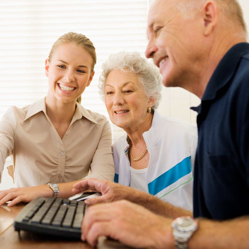 young woman helping older couple on computer