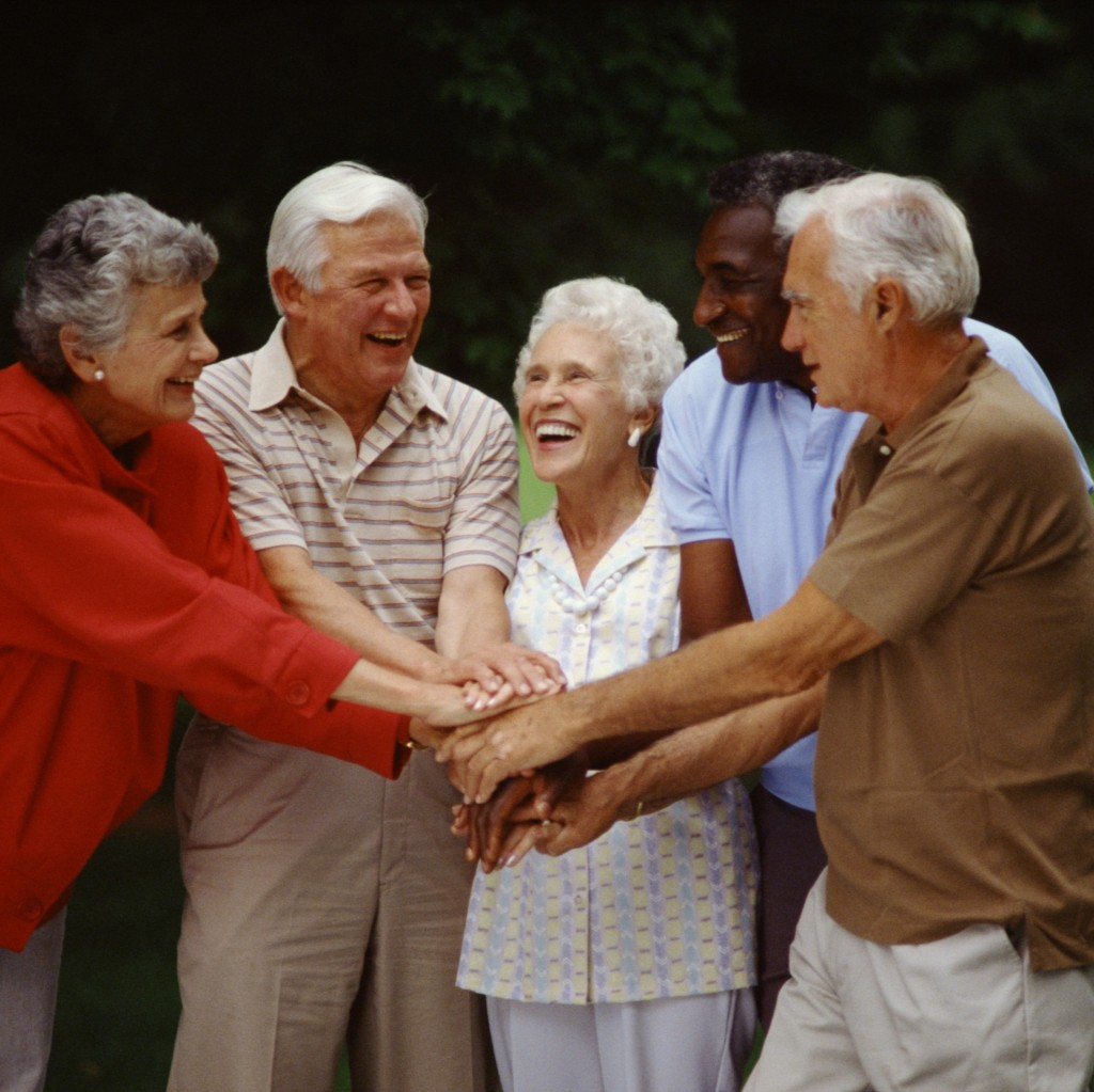 group of seniors with hands in centered circle